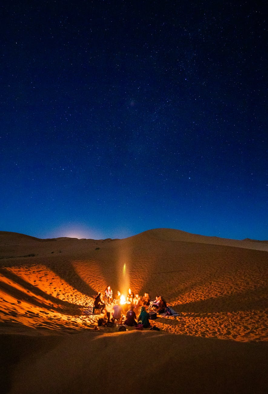 Moroccan people sitting in front of bonfire in desert during night-time in Morocco